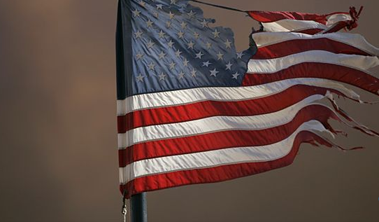 Image of a torn and tattered American flag.