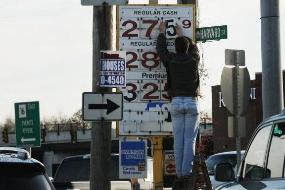 man changing gas sign