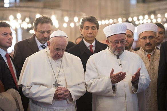 Pope Francis prays with Istanbul's grand mufti Rahmi Yaran during a visit to the Sultan Ahmed Mosque, also known as the Blue Mosque, in Istanbul Nov. 29. (CNS photo/L'Osservatore Romano via Reuters) See POPE-ISTANBUL Nov. 29, 2014.